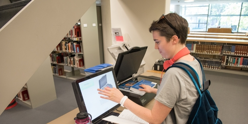 a Smith College student scanning a book with scanning equipment