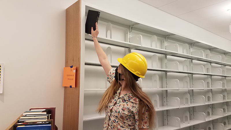 young woman with long blond hair putting a book high on a metal book shelf