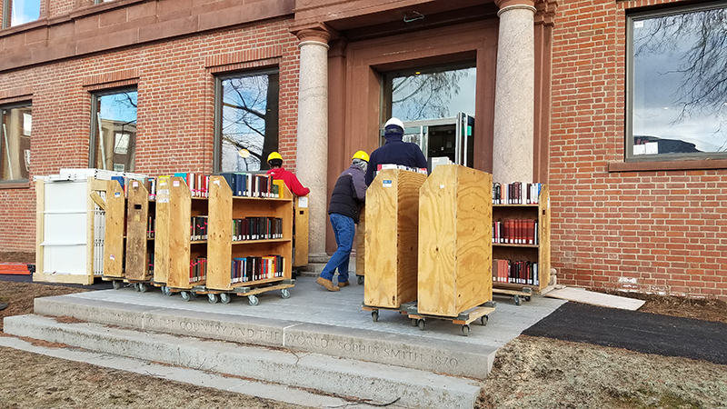 workers line up carts full of books outside the Neilson Library