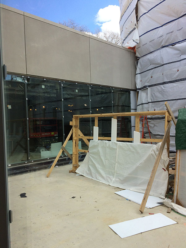 View from the sunken courtyard showing new precast concrete panels and the glass panels allowing light into the below grade spaces. This view is looking towards College Hall