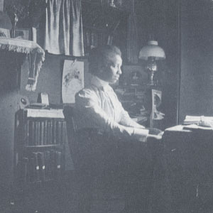 Otelia Cromwell sitting at her desk in 1900