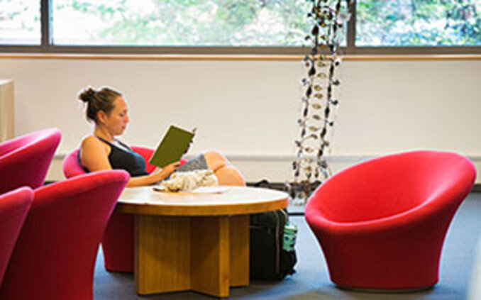 Student studying in red chair in Hillyer Art Library