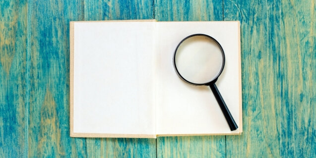 a book laying open with a magnifying glass on it