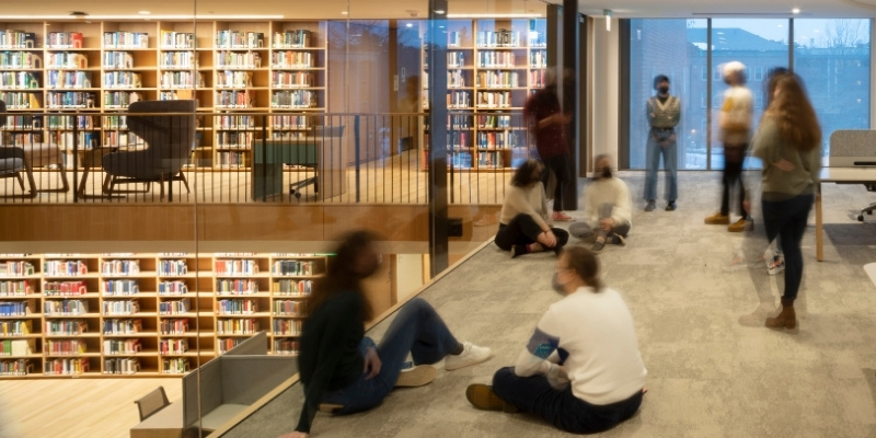 students walking near bookcases in the Neilson Library