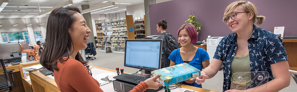 Student checking out a book at the service desk in Young Library