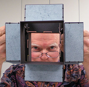 Daniel E. Kelm peering through one of his wire edge models, Metamorphic Book