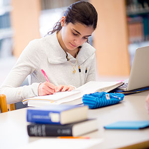 Student working at a table with library materials