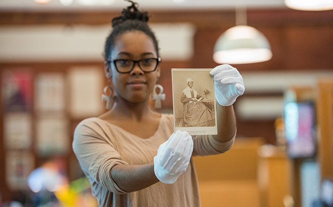 Student in Special Collections with photo of Otelia Cromwell