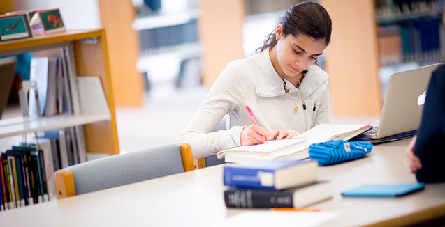 Student working at table with books