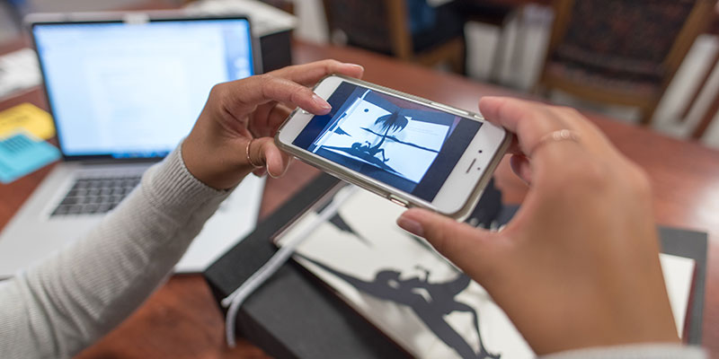 Researcher using mobile device and camera in the Special Collections reading room